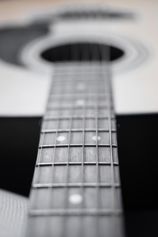 Guitar detail neck. Guitar detail closeup of fret and fretboard, pins and bridge pins, strings and saddle and sound hole stock images