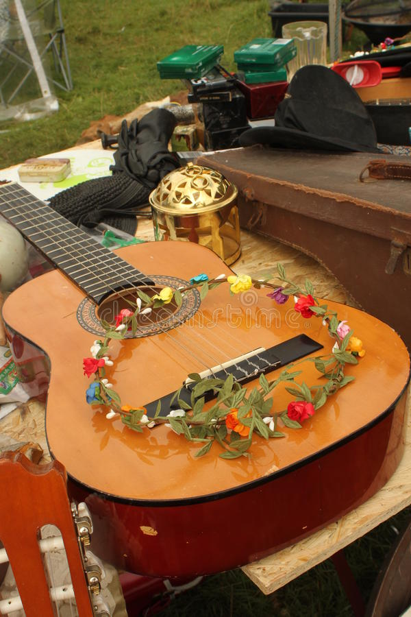 Guitar and flower crown at a festival. Acoustic guitar and pretty hand made flower crown for sale at at Somersault music and outdoor festival in July 2014 royalty free stock photo
