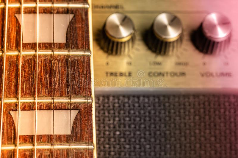 Guitar fretboard and fret marker detail, blurred old amplifier knobs in the background. Guitar fret board and fret marker detail, blurred old amplifier knobs in royalty free stock image