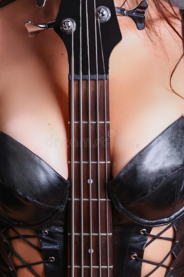Guitar fretboard sandwiched between her breasts. Boobs stock images