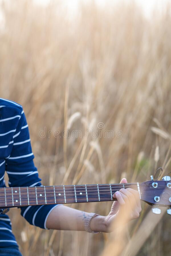 Close up of a hand with a guitar in a brown meadow background royalty free stock photos
