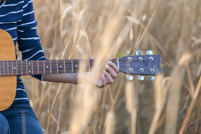 Close up of a hand with a guitar in a brown meadow background stock photos