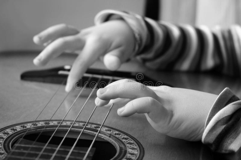 Guitar in the hands of a child of a little boy playing music. Black and white stock image
