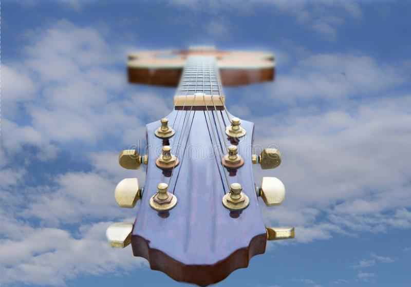 Guitar Head and Neck to the Sky cloudy and Blue. Looking down an accoustic guitar head and neck to the blue sky . There is space for text on each side of the stock photos