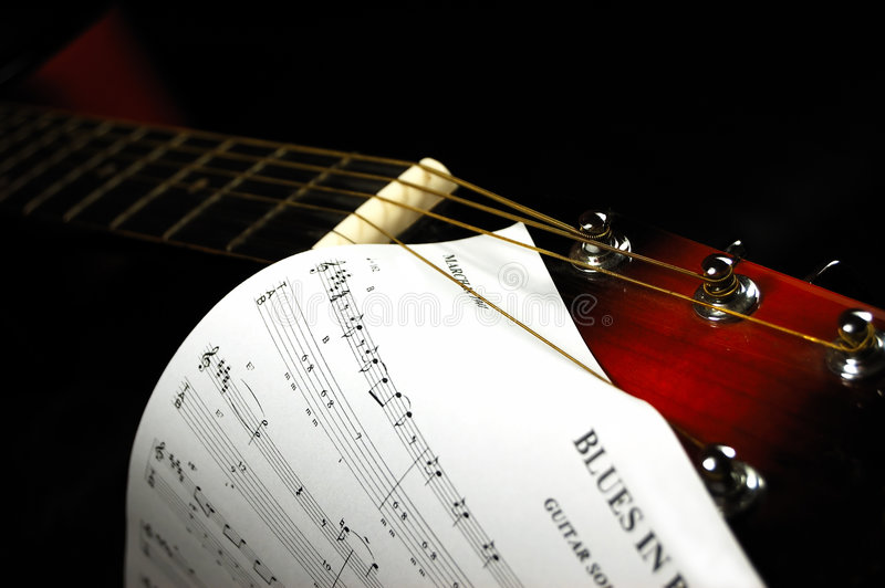 Guitar headstock with a blues sheet music. Blues time. Guitar headstock with a blues sheet music. Low key lighting stock images