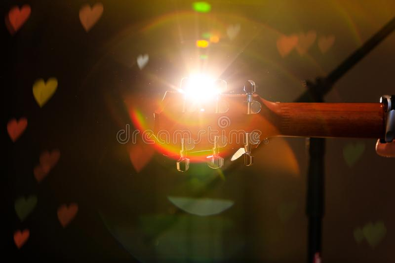 Guitar headstock on concert stage background with hearts light flare effect. Back view of guitar headstock during spectacle. Best. Conceptual picture for stock photography