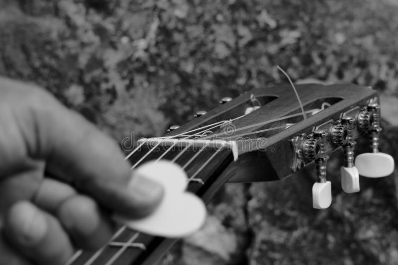 Love to Pick. A Guitar Headstock, Showing the Tuning Pegs and Machine Heads of the acoustic  Instrument with a Blurred Foreground Hand Holding a Love Heart Pick stock images