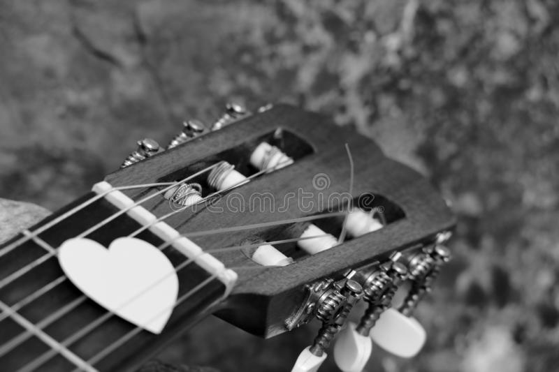 Love to Pick. A Guitar Headstock, Showing the Tuning Pegs and Machine Heads of the acoustic  Instrument with a Blurred Foreground Hand Holding a Love Heart Pick stock photos