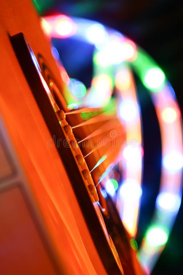 Guitar and leds light on party. Close-up on easel of guitar royalty free stock image