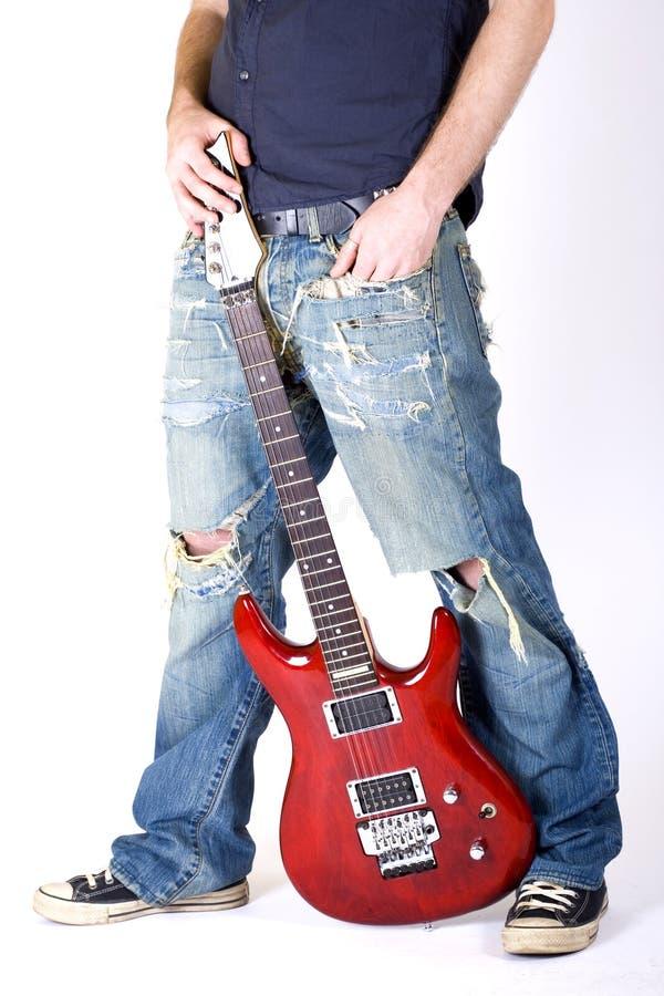 Guitar between the legs of a guitaris stock images