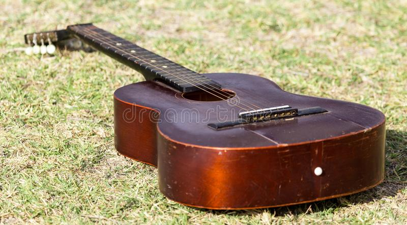 Guitar lying on the grass on the nature stock photos