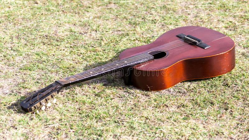 Guitar lying on the grass on the nature royalty free stock images