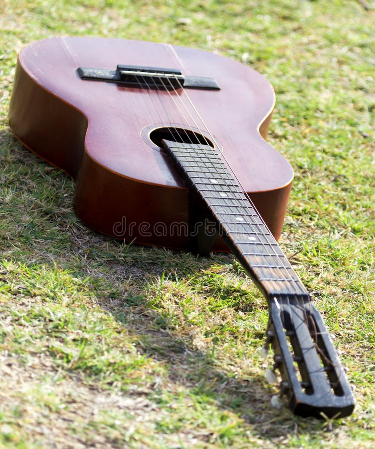 Guitar lying on the grass on the nature royalty free stock photography