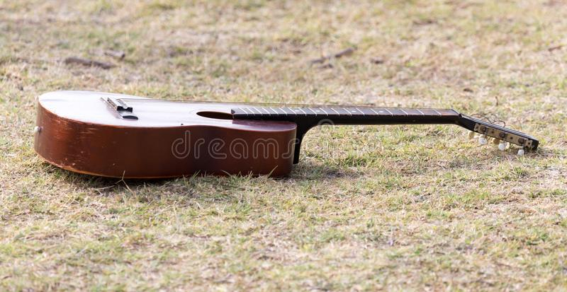 Guitar lying on the grass on the nature stock images