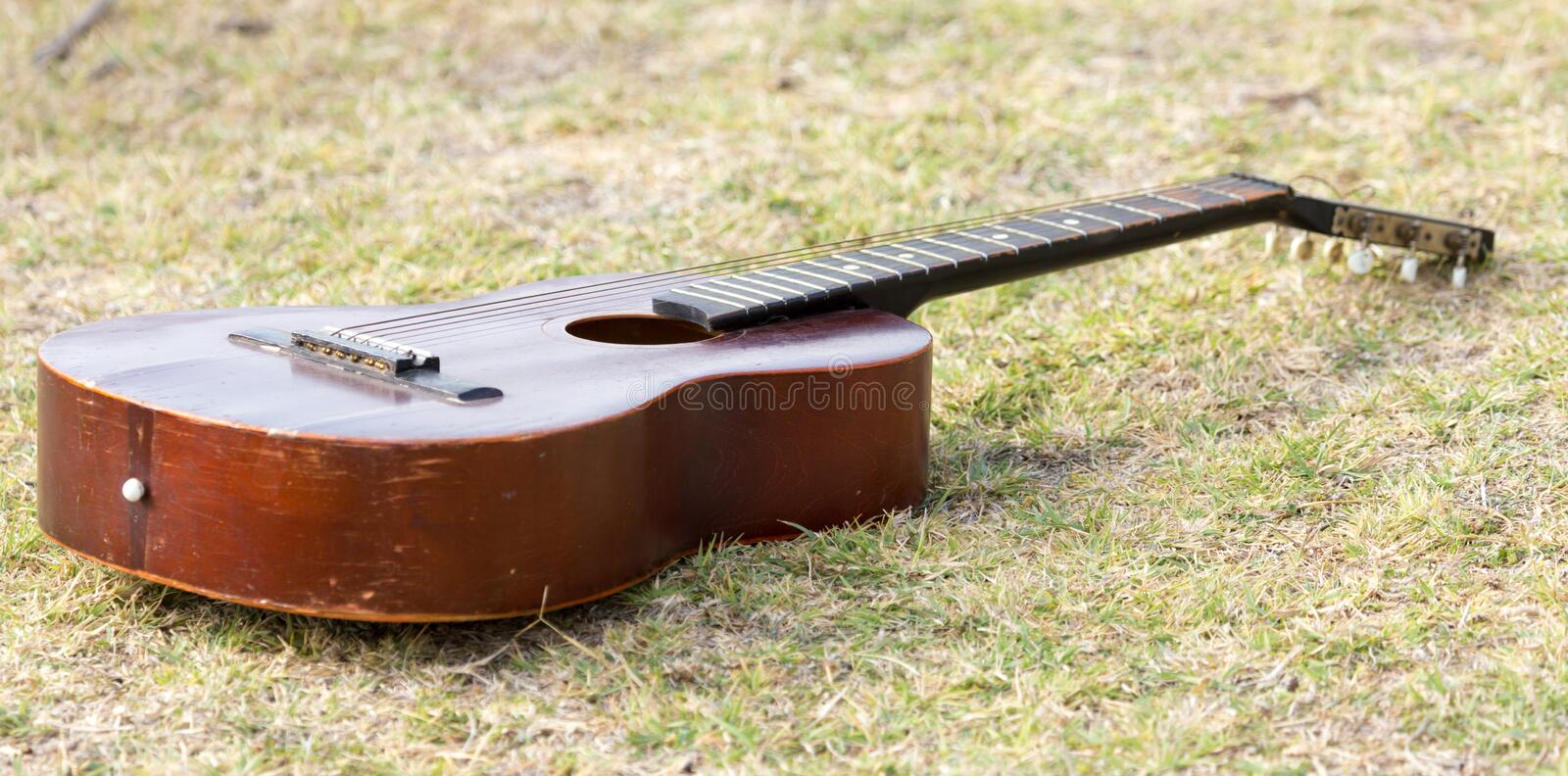 Guitar lying on the grass on the nature stock photography