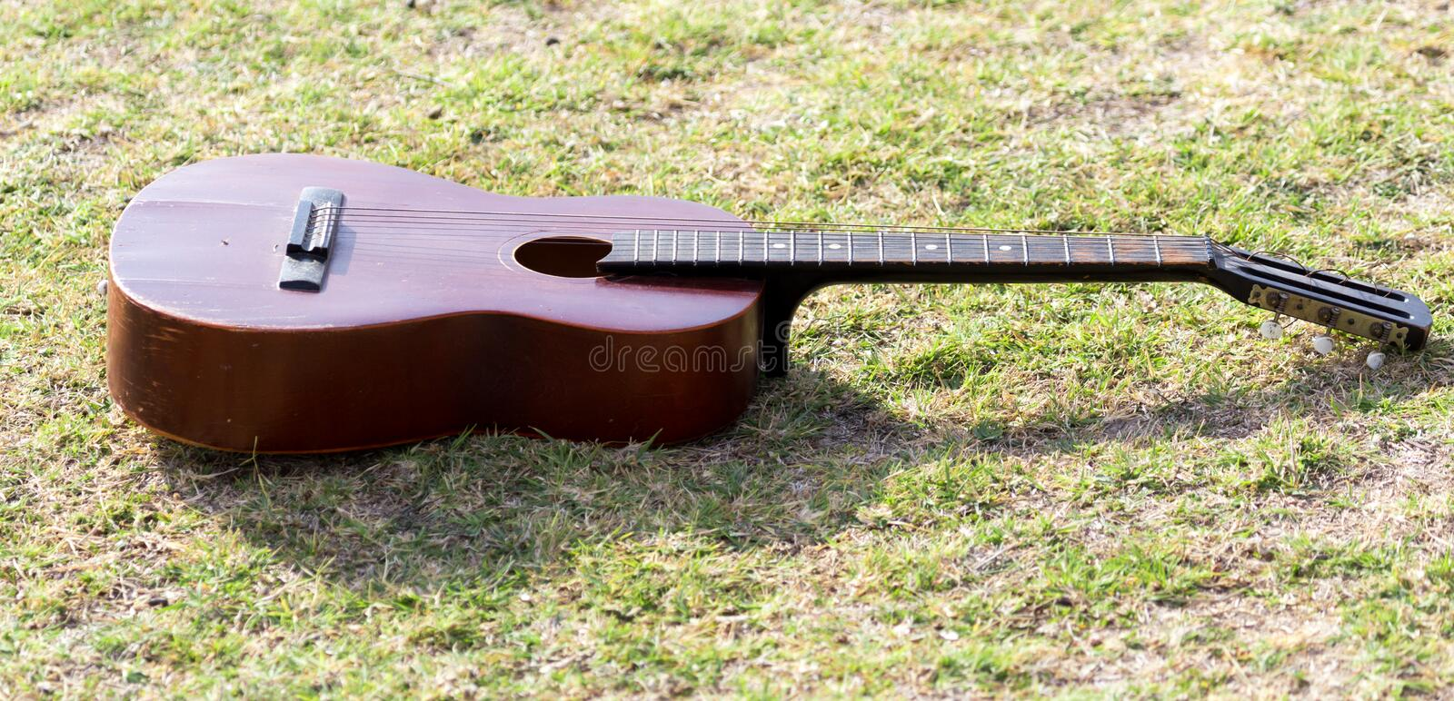 Guitar lying on the grass on the nature royalty free stock image
