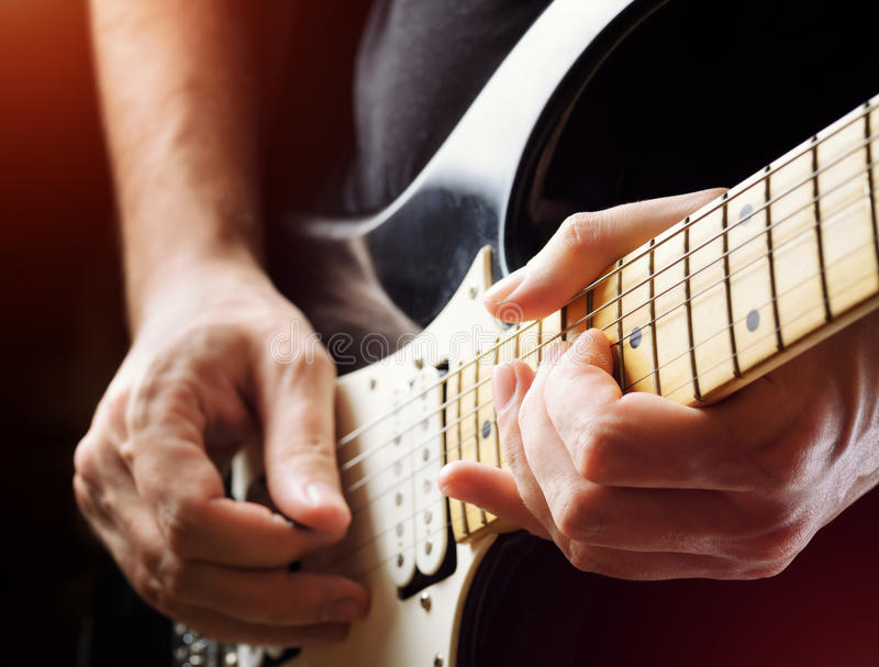 Man playing guitar on a stage. Musical concert. Close-up view stock photo