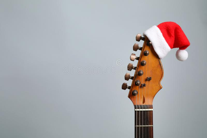Guitar met Santa hat op grijze achtergrond kerstmuziek royalty-vrije stock afbeelding
