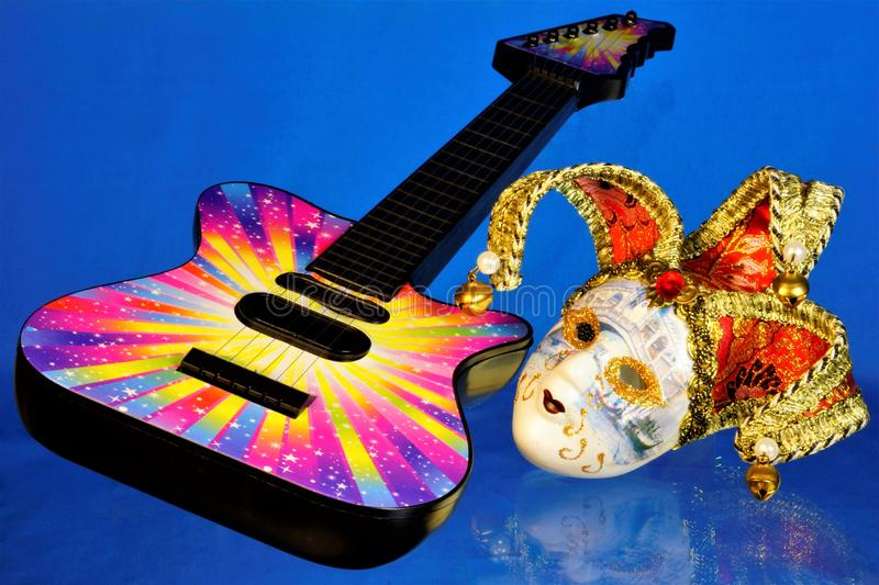 Guitar musical instrument, mask cheerful carnival performance. The mask is a symbol of theatrical transformation, change and stock photos