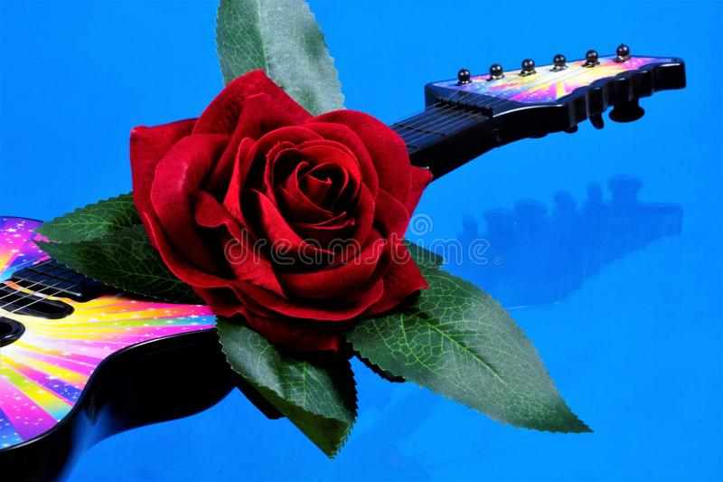The guitar is a musical instrument and a red rose the Queen of flowers. Rose is a symbol of love, passion, decoration of holiday royalty free stock images