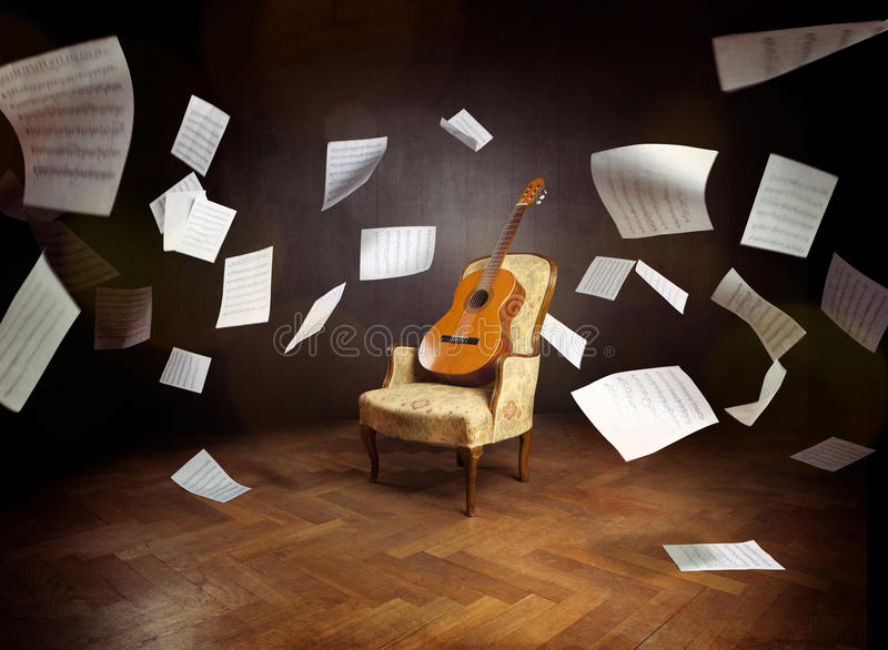 Guitar on an old chair with flying music sheets stock photo