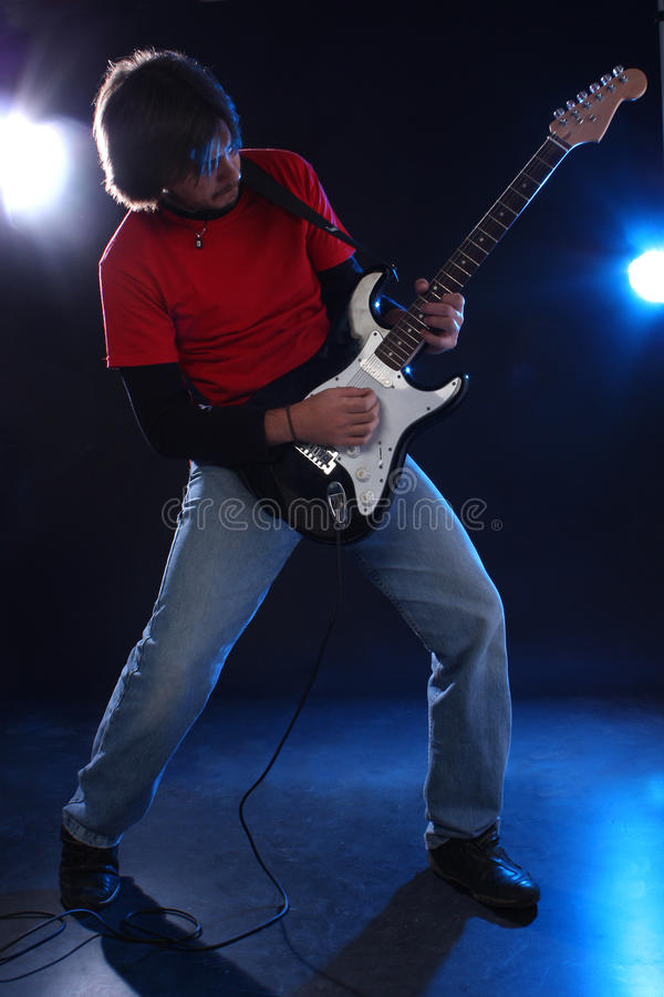 Guitar player. Musician playing electric guitar on stage royalty free stock photo