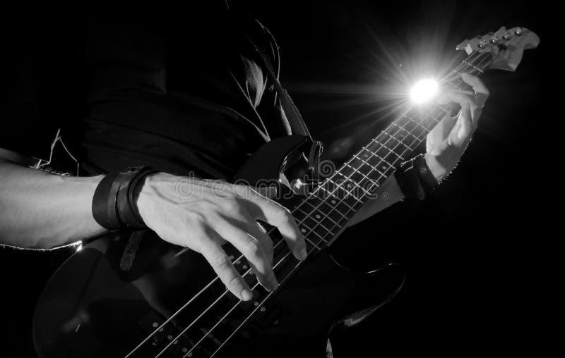 Guitar player with bass guitar. Closeup of guitar player with bass guitar on stage stock image