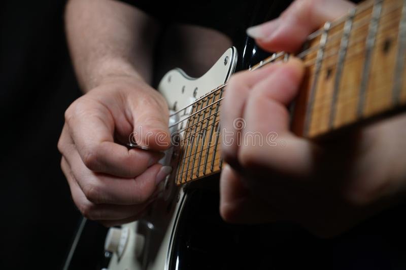 Guitar player on black background royalty free stock photography