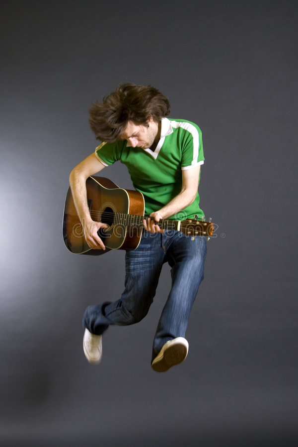 Guitar player jumping in midair royalty free stock image