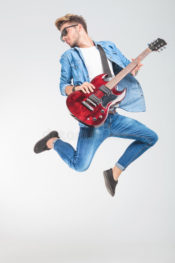 Guitar player jumping while playing rock and roll royalty free stock image