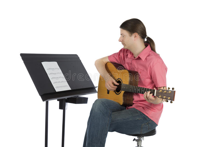 Guitar player playing and following the notes royalty free stock images