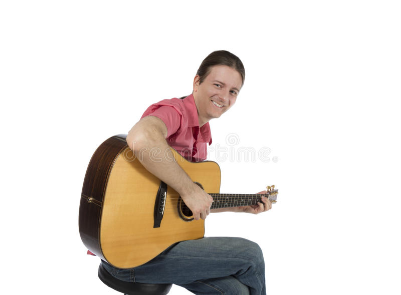 Guitar player playing his acoustic guitar with a smile stock photo