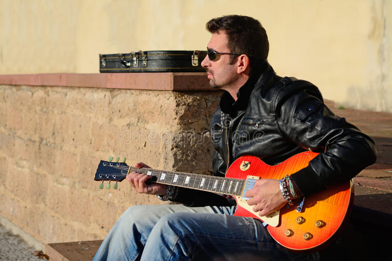 Guitar player at sunset. Guitar player with electric guitar at sunset royalty free stock photography
