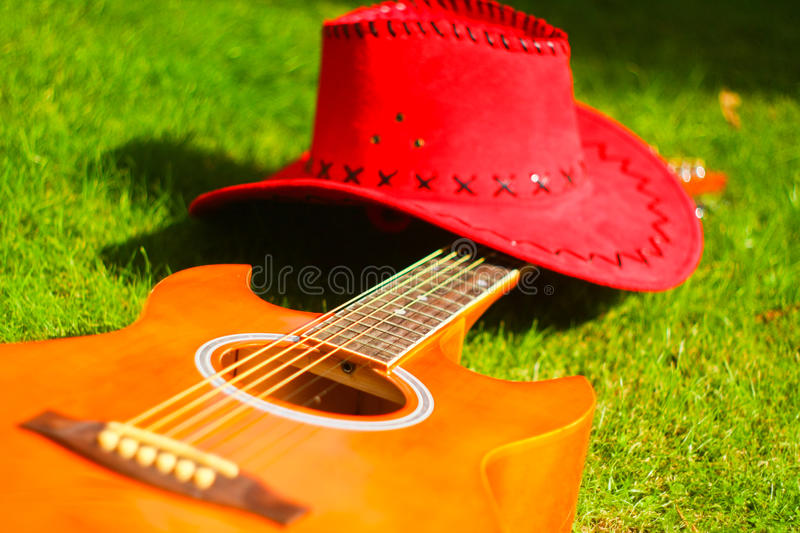 Guitar and red hat. Photo with red hat and guitar on the grass stock photo