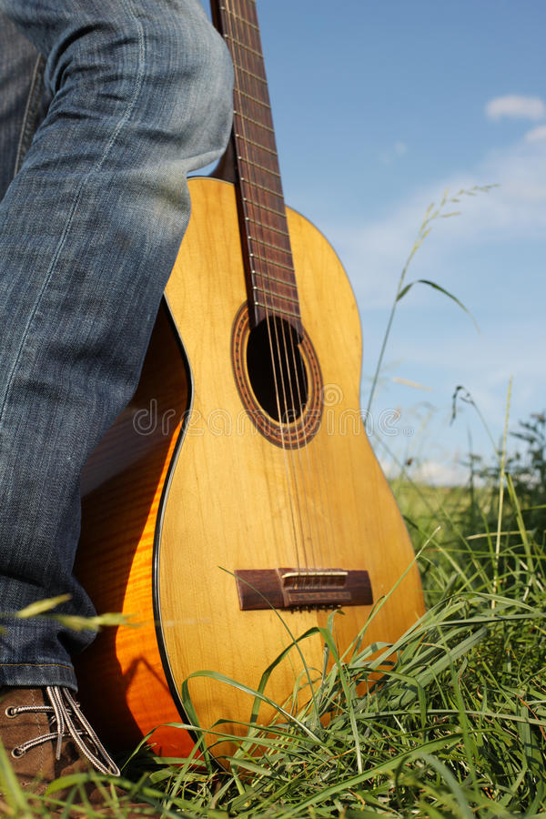 Guitar resting on a mans foot stock image