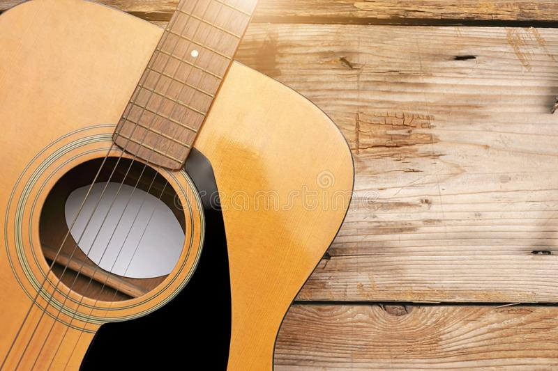 The guitar rests on a wooden floor. Copy space royalty free stock images