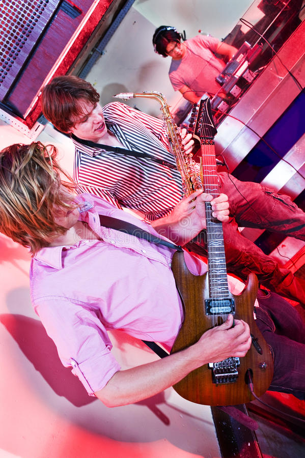 Guitar, Sax and DJ. Live act in a club with a saxophonist, guitarist and DJ royalty free stock photos