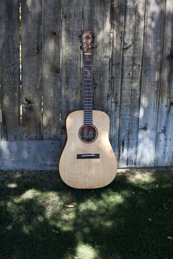 Guitar in the Shade Against a Fence royalty free stock image