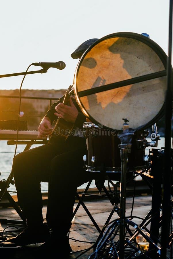Guitar-spelare och sångare vid solnedgång arkivbilder
