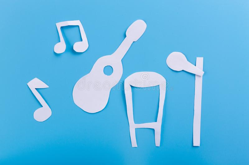 Guitar on stage. Blue background. paper cut stock images