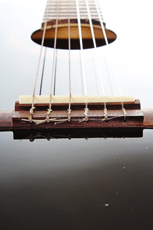 Guitar string closeup. POV artsy black shiny reflective guitar studio photo. stock photos