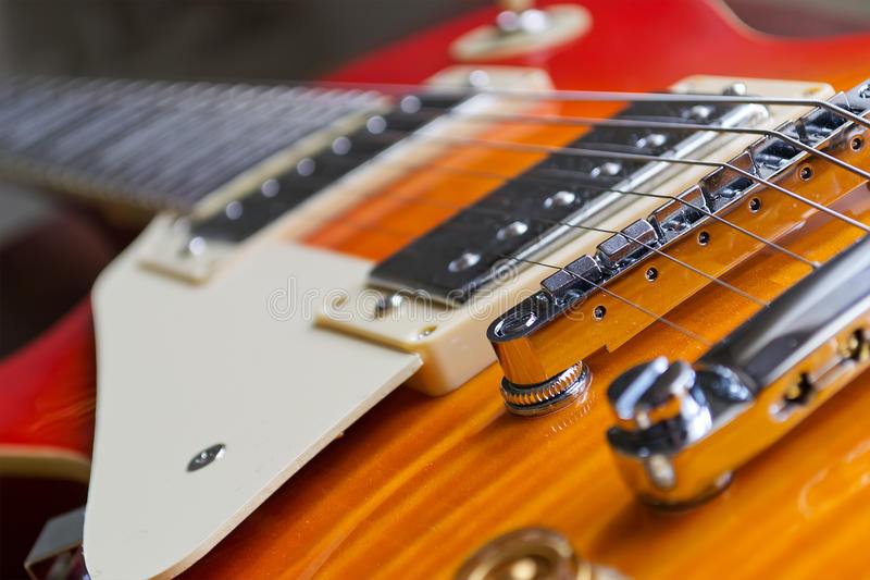 Guitar strings. Closeup of a guitar bridge with control knobs stock images