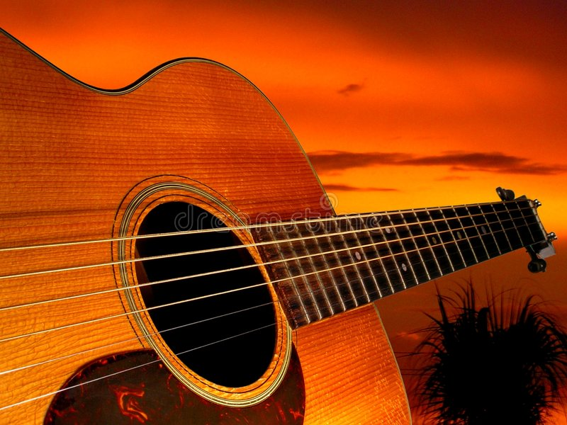 Guitar Sunset. The bridge of an acoustic guitar points off into the sunset royalty free stock photos