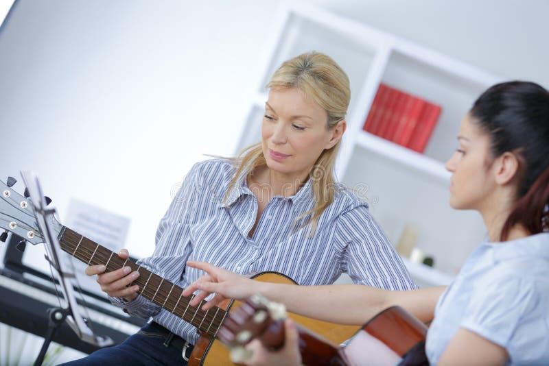 Guitar teacher teaching girl royalty free stock photo