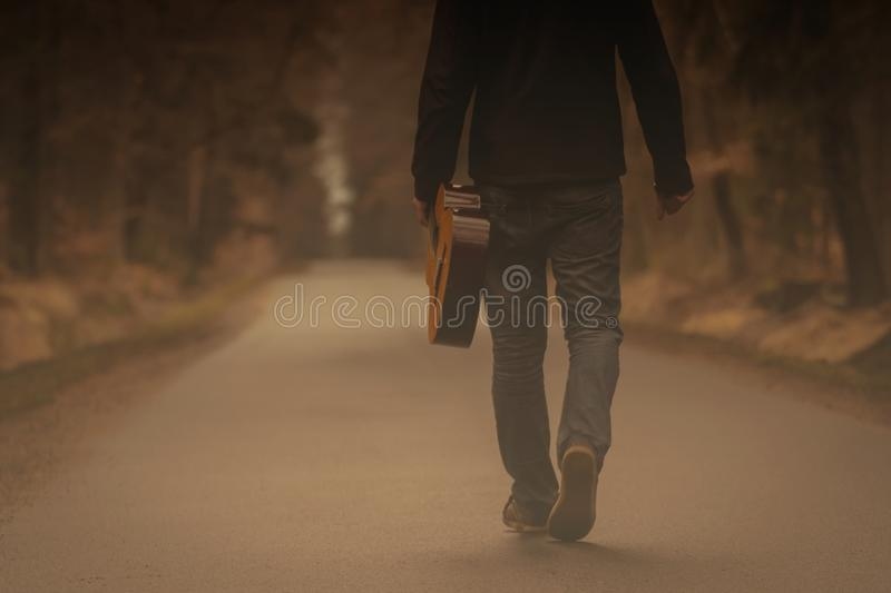 With guitar on the way. Men on the way with guitar. Free travel with country guitar in forest royalty free stock image