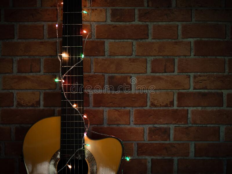 Guitar wrapped with glowing string lights on brick wall. Acoustic guitar wrapped with glowing string lights on brick wall royalty free stock photo