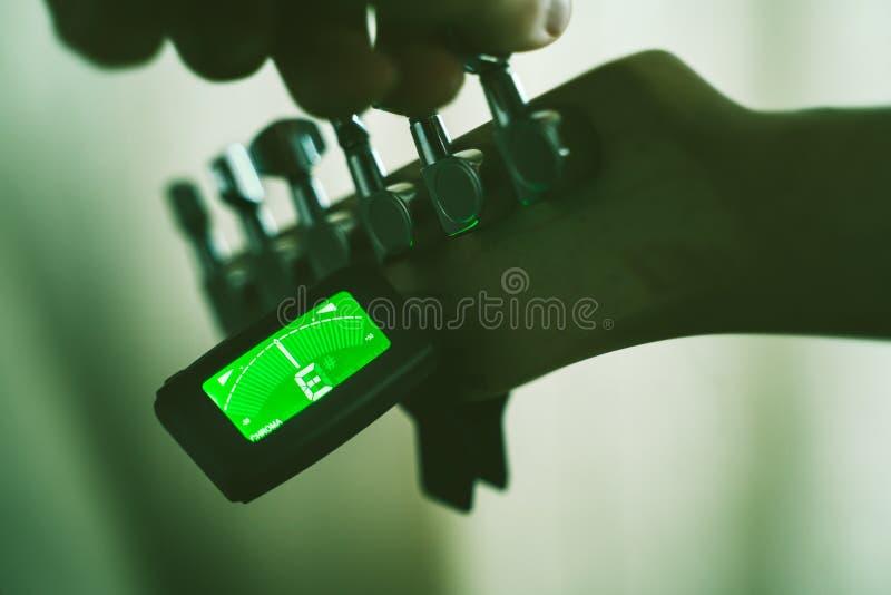 Guitare électrique de accord avec le tuner chromatique image stock