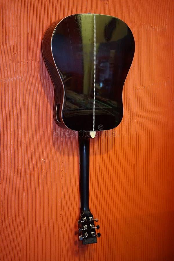 Guitare accrochant sur un mur images libres de droits