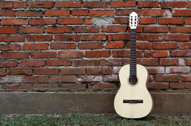 Guitare acoustique se penchant sur le mur de briques rouge grunge Herbe sur le trottoir photos stock