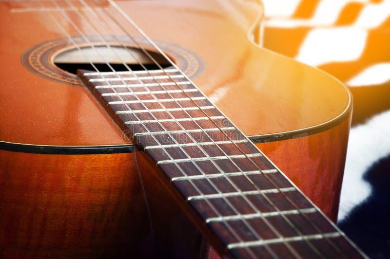 Guitare acoustique sur un lit blanc photographie stock libre de droits